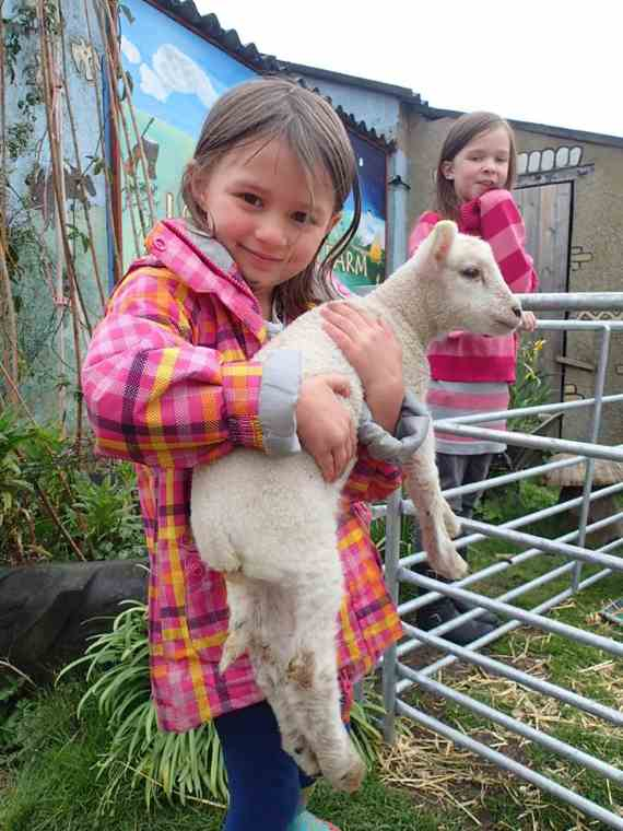 Image of young girl in orange coat and blue leggings holding a lamb in her arms in front of farm building