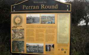 Image of notice board showing information on Perran Round in front of hedge