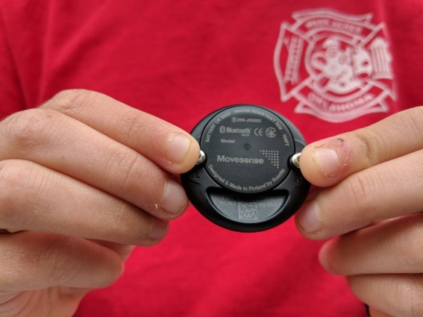 Image of close-up fingers holding black disc with two metal studs on, on red background
