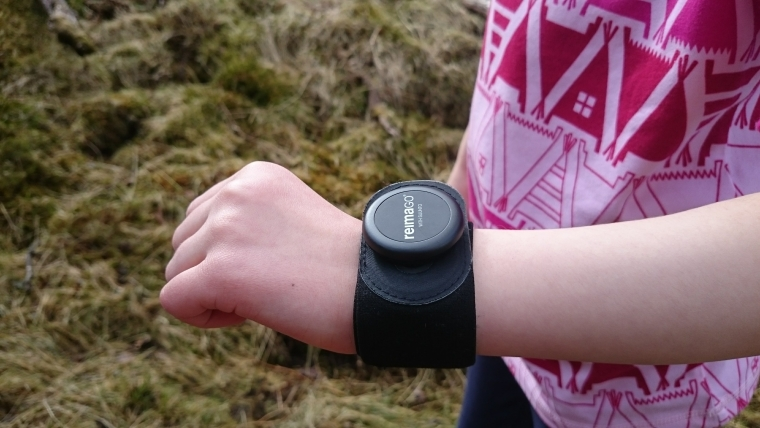 Image of child's wrist with black watch-like strap bearing words ReimaGO, with pink sleeve rolled up and grass in background