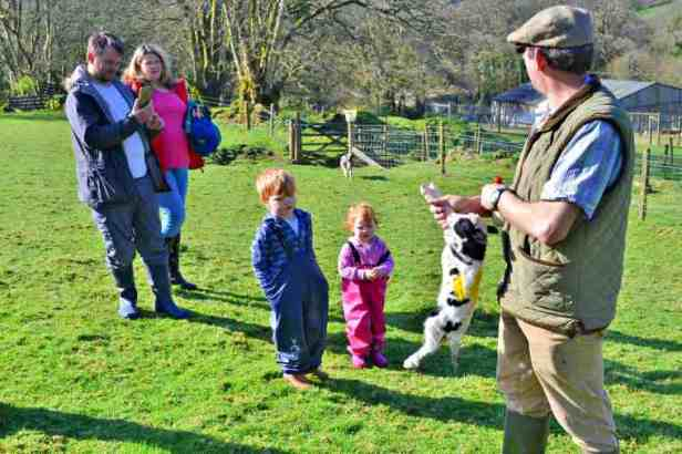Image of farmer in flat cap holing newborn lamb by front legs with families and kids looking on in field