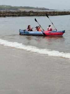 Image of three girls in inflatable canoe on sea with rocks and headland behind