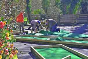 Image of two men and a boya t work fixing green baize in a kids crazy golf play area