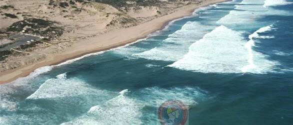Image of wide sandy beach with white water either side of smooth water in centre