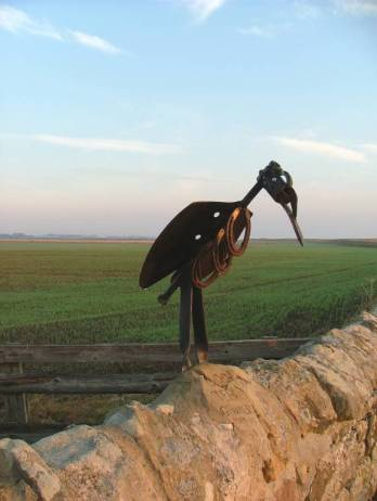 Image of brown rusted metal sculture of stylised crow sat on dry stone wall with sprouting grass in field behind