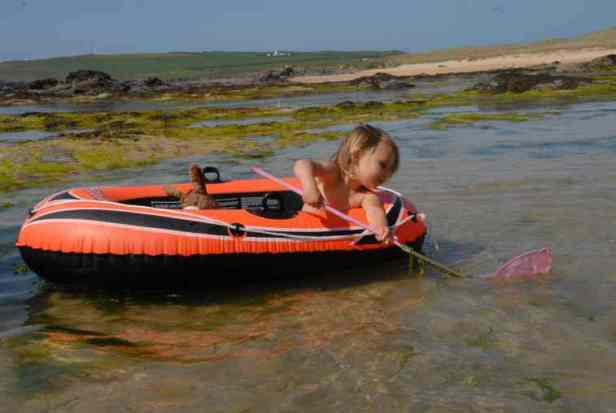 Image Of Toddler Holding Fishing Net While Sitting In Inflatable Dinghy In Shallow Rockpool At Beach