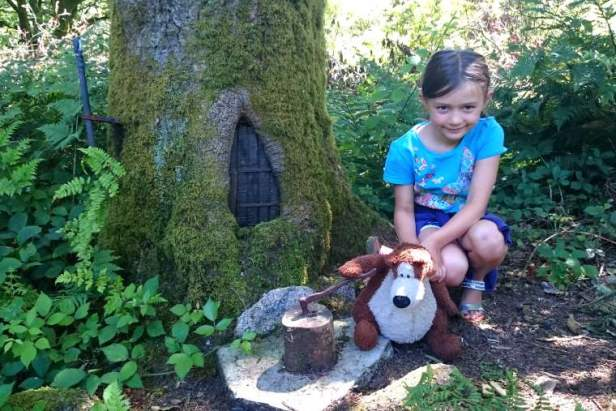 2Image of girl in blue top squatting by trees with a fairy door in the trunk in a wood holding a brown teddy who is chopping with a mini axe