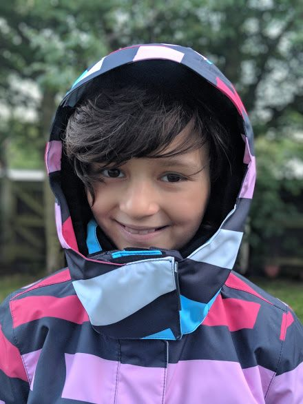 Image close up of smiling dark haired girl wearing pink, blue, black and white patterned winter ski jacket with hood up