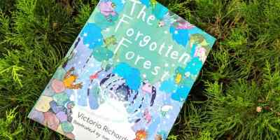 Image of children's picture book entitled The Forgotten Forest lying on green evergreen bush