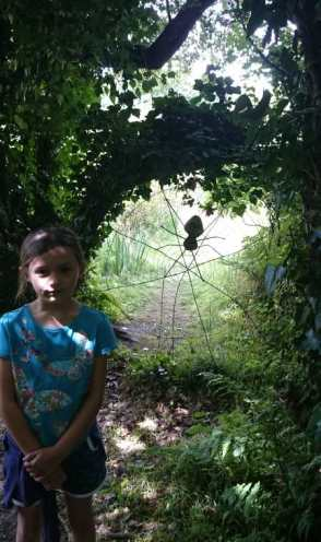 Image of girl with worried look on face standing in front of giant spiders web between trees in shady woodland
