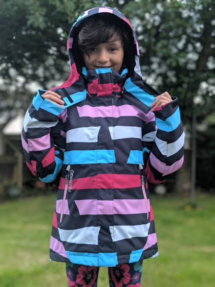 Image of smiling dark haired girl holding hood straps of white, black, pink and blue winter outdoor ski jacket in garden