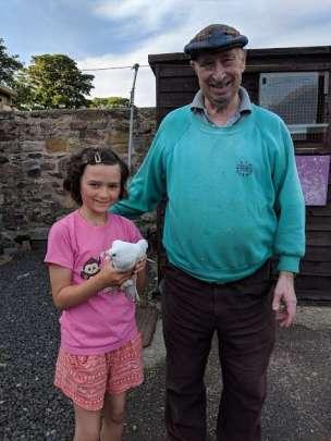 Image of smiling girl in pink top holding white dove next to man in green top and cap in front of wooden bird shed