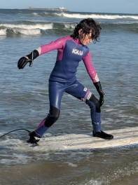 Image of girl in blue and pink Iglu wetsuit standing on surfboard on a wave in the sea