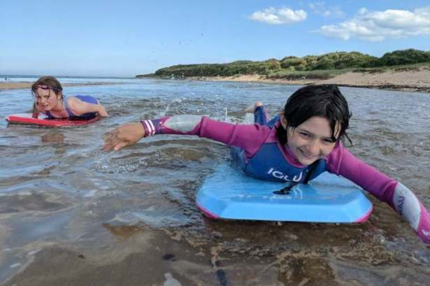 Image of girl in blue and pink wetsuit on bodyboard with girl in swimsuit on bodyboard to side on beach with dunes behind
