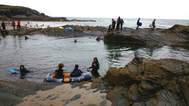 Image of lots of people in wetsuits, swimsuits with a dingy in a large outdoor rockpool with sea behind