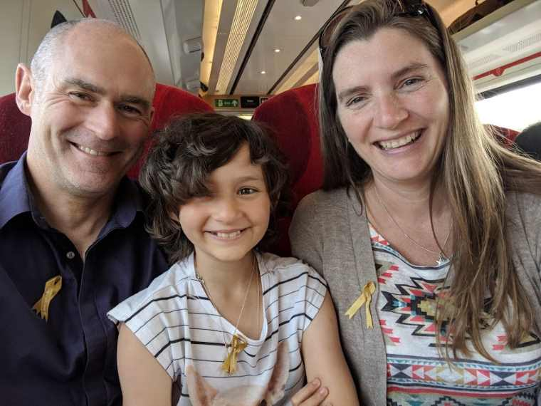Image of man, girl and woman grinning on seats in a train, wearing gold ribbons for childhoood cancer awareness month
