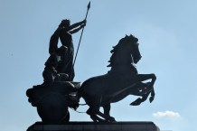 Image of silhouetted statue if Boudica on chariot being pulled by horse with blue sky behind