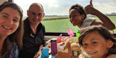 Image of smiling man, woman and two girls with thumbs up sitting at table on train with fields in window behind
