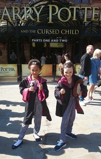 Image of two girls in black robes carrying wands standing outside building with Harry Potter sign behind