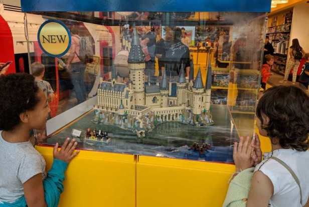 Image of two girls looking through glass display case at lego model of Harry Potter Hogwarts Castle