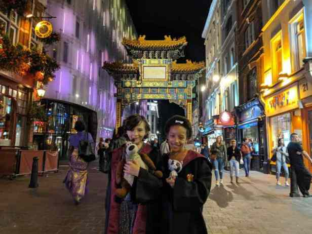 Image of two girls with teddies wearing Harry Potter robes in street at night with Chinese pagoda arch behind