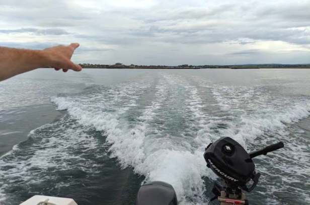 Image of wake behind boat with small motor showing at bottom right and distant land on horizon with man's arm pointing to land