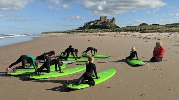 Group of children in wetsutis with green surf boards practising standing technique on the beach with instructor in red and castle behind