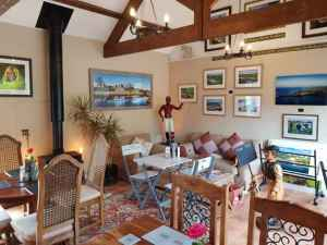 Image of cafe room with tables, chairs, beams, log burner and art on walls