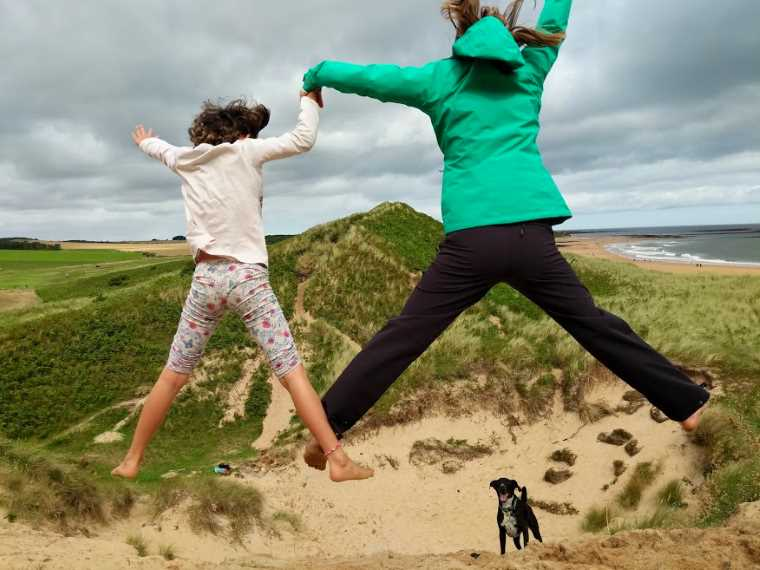 Image of child in light top with woman in green jacket and dark trouses doing scissor jumps from high spot in sand dune with dune and sea behind