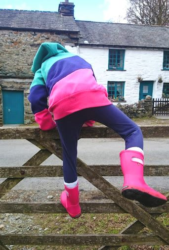 Image of child in pink boots, blue leggings and red and green top climbing over wooden five bar gate with cottage behind