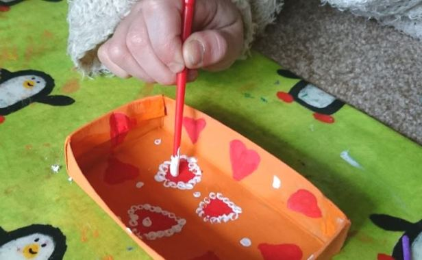 Painting the inside of a matchbox memory box with hearts and dots