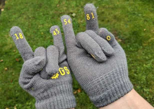 Image of close up of one adult hand, one child hand both wearing grey gloves with yellow numbers on fingertips