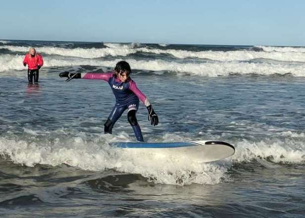 Image of girl in blue and pink wetsuit standing on surfboard on wave with instructor in red jacket behind