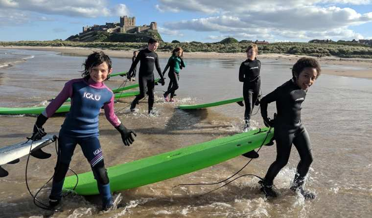 Image of girl in blue and pink wetsuit with other kids in black wetsuits dragging green surfboards from sea with castle and dunes in background