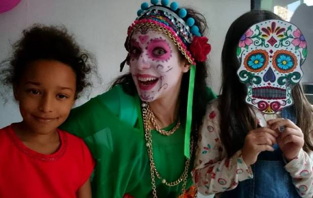 Image of girl in red dress next to woman in green Day of the Dead costume & headdress and girl holidng coloured sugar skull face mask in front of face