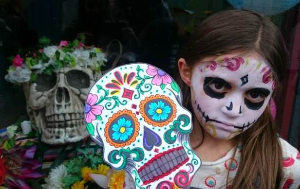 Image of girl with Day of the Dead Catrina sugar skull facepaint holding sugar skull mask next to model skull wearing flower headband