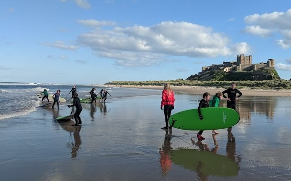 Image of group of children carrying surfboards walking out of the sea in front of dunes and castle