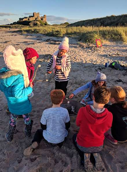 Image of group of children in warm clothes on a beach cooking marshmallows over a firepit with dunes and castle in background