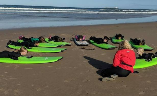 Image of instructor in red top and children in wetsuits on green surfboards on sand with sea behind