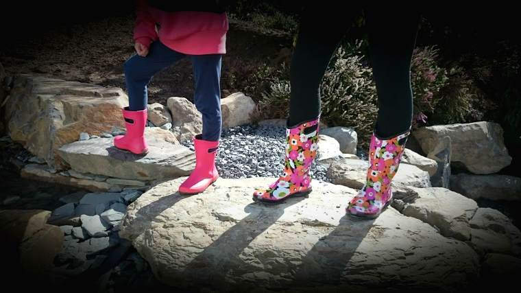 Image of legs and feet of adult wearing pink and black floral boots and child wearing pink boots standing on rocks