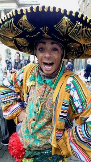 Image of man in gold decorated black Mexican hat and gold Day of the Dead carnival costume grinning at camera in crowd in street