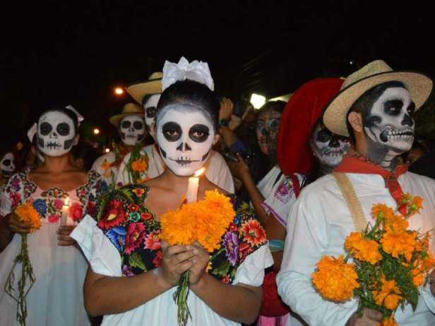 Image of men and women in white clothes with white skull facepaint carrying candles and orange marigolds