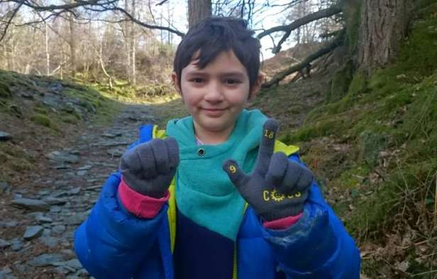 Image of short haired girl in blue jacket holding up hands in woodland wearing grey gloves with yellow numbers on each fingertip