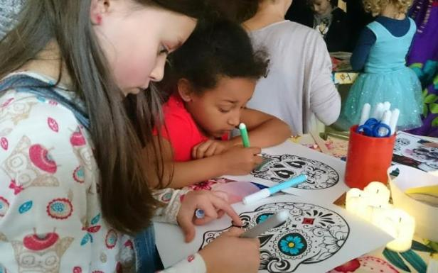 Image of two girls sat at a table colouring in Day of the Dead sugar skull masks