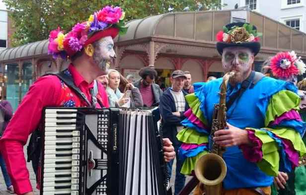 Image of two men in bright day of the dead costumes playing accordion and saxophone at outdoor street carnival celebration