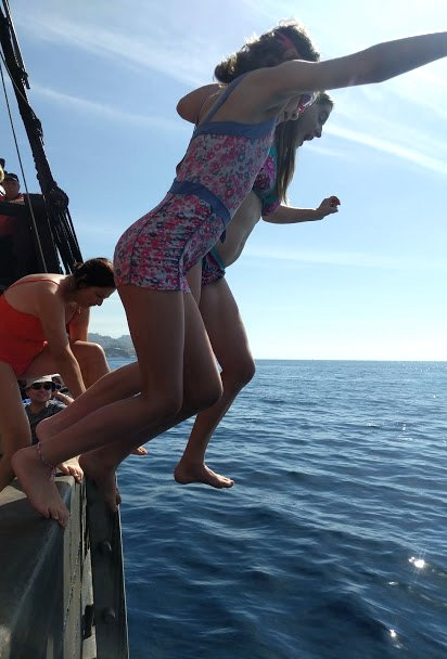 Image of woman and child in swimsuits jumping from side of boat into blue sea