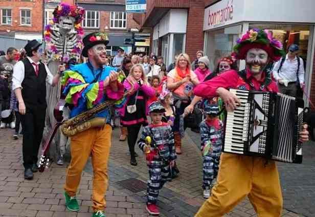 Image of crowd in street dancing to music played by two men in coloured day of the dead costumes on accordion and saxophone with skeleton puppet behind