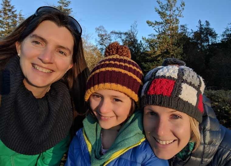 Image of 3 girls taking selfie with trees in background