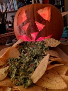 Image of carved pumpkin spewing guacamole 'vomit' with tortilla chips