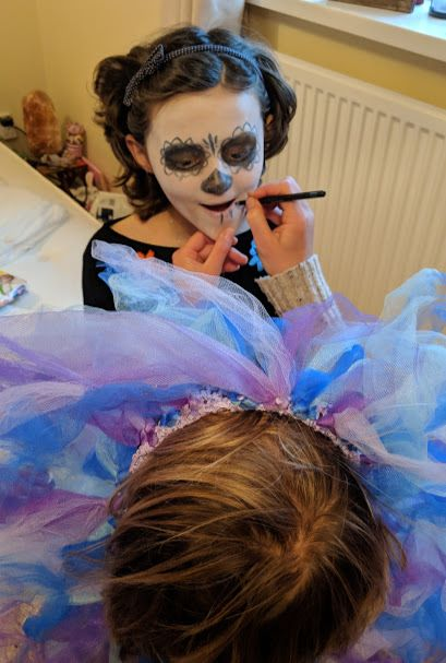 Image of girl having black and white face paint put on by woman